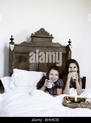 Two girls having a cup of hot chocolate in a rustic bed, Italy. - Stock Photo
