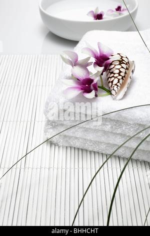 Handtuecher mit Orchidee und Muschel, im Hintergrund Porzellanschale mit Wasser - Stock Photo