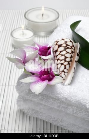 Handtuecher mit Orchidee und Muschel, im Hintergrund Teelichter - Stock Photo