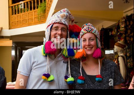 A young couple trying on Peruvian hats at the Pisac market, Peru - Stock Photo