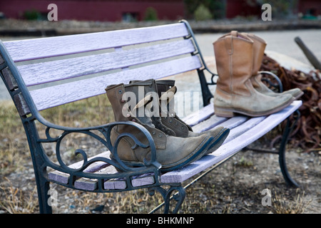 Old work boots sit on a bench in Buena Vista, Colorado. - Stock Photo