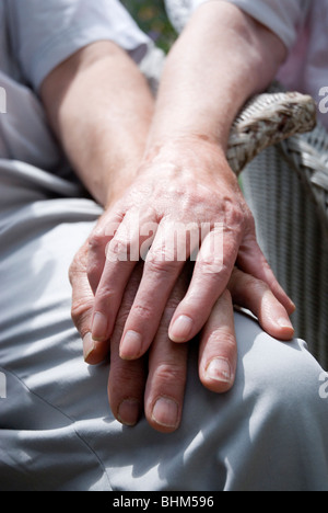Cropped image of elderly couple holding hands. - Stock Photo