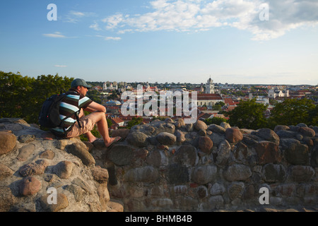 Man Sitting On Walls Of Gediminas Castle Overlooking Old Town, Vilnius, Lithuania, Baltic States, Eastern Europe - Stock Photo