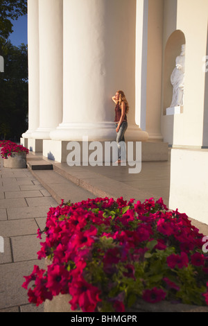 Woman Standing Between Pillars Of Vilnius Cathedral, Vilnius, Lithuania, Baltic States, Eastern Europe - Stock Photo
