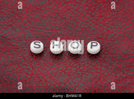 The word shop is part of this series on black and white round lettering beads on a black and red leather textured - Stock Photo