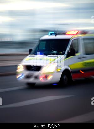 Ambulance motoring along street with lights flashing - Stock Photo