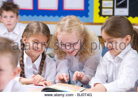 School girls smiling and reading book in classroom - Stock Photo