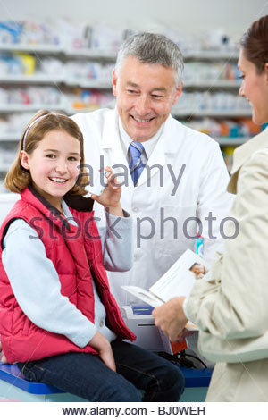 Pharmacist helping girl with asthma inhaler as mother watches - Stock Photo