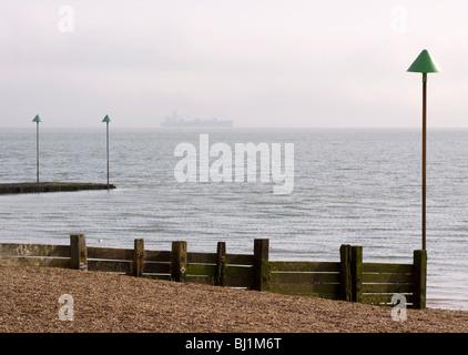 Wooden groyne on the beach at Leigh-on-Sea with a ship on the horizon. Leigh-on Sea, Essex, England - Stock Photo