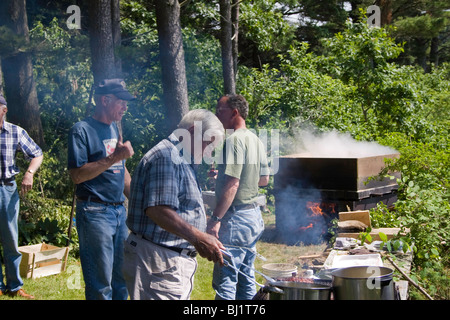 Cooks prepare steaks, corn-on-the-cob, and lobsters for a summer social at Sawyers Island, Maine - Stock Photo