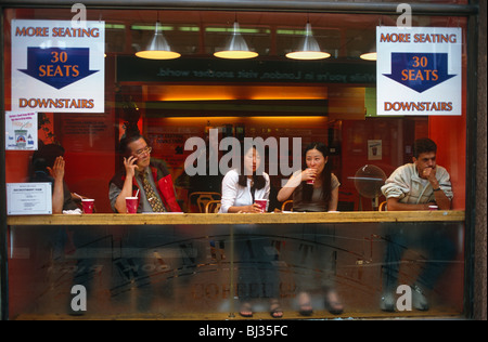 Five customers are seated in the window of the Manhattan Coffee Company on Shaftesbury Avenue, in London's Chinatown. - Stock Photo