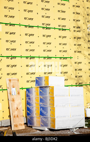 Pile of polystyrene ground frost insulation slabs and the wall lined with Isover mineral wool insulation panels - Stock Photo