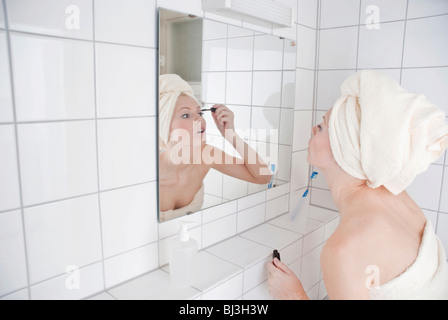 Women putting on mascara in front of the mirror in the bathroom - Stock Photo