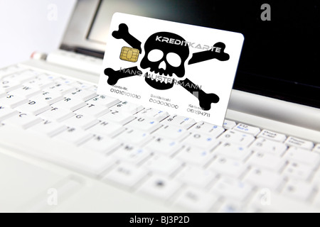 Credit card with a skull at a PC, notebook, symbolic image for the risk of data misuse when online shopping, data - Stock Photo
