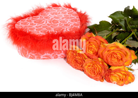 Hear shaped gift box and bunch of orange roses isolated on white background Conceptual still life - Stock Photo