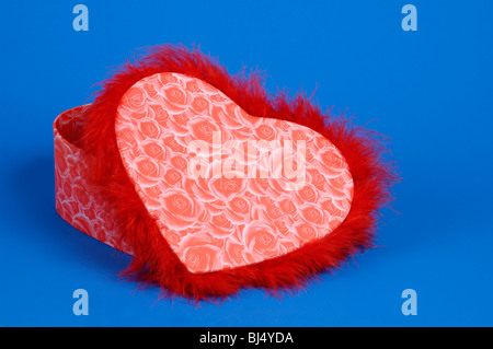 Lovely heart-shaped red fancy box isolated silhouette on blue background. Valentine's Day gift concept - Stock Photo