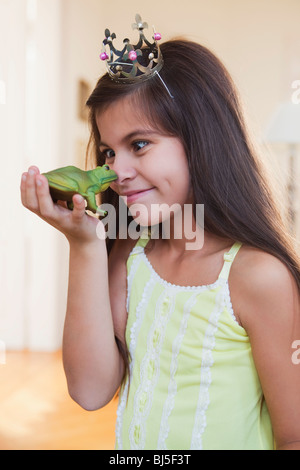 girl wearing crown playing with toy frog - Stock Photo