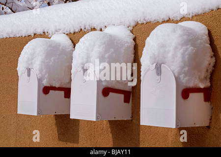 Three white mailboxes built into adobe wall covered with snow. - Stock Photo