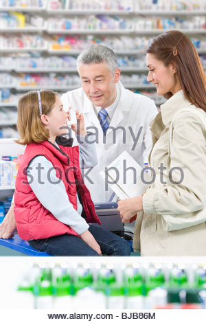 Daughter taking asthma inhaler as mother and pharmacist watch - Stock Photo