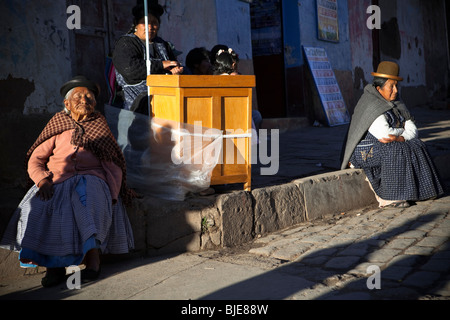 Women in traditional clothes taking sun in a street of Copacabana, Titicaca Lake, Andes, Bolivia South America - Stock Photo