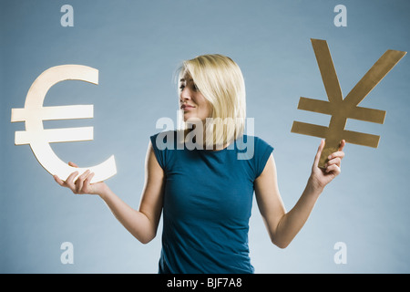 woman holding up currency symbols - Stock Photo