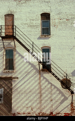 Old building in rural town with fire escape staircase ladder. - Stock Photo