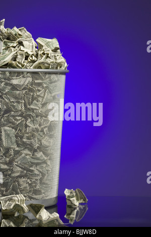 Crumpled money in waste paper basket - Stock Photo