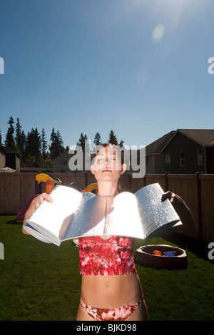 Woman sunbathing in lawn chair with boy and girl playing in yard - Stock Photo