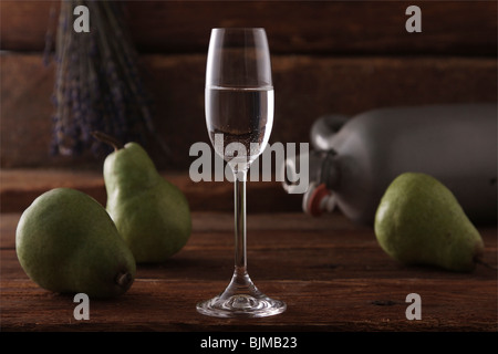 Glass of pear brandy with pears and a whiskey jar on a rustic wooden background - Stock Photo