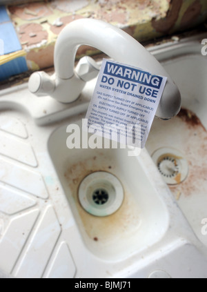 DOMESTIC HOUSEHOLD TAP AND SINK UNIT  WITH 'WARNING DO NOT USE' STICKER ON IT - Stock Photo