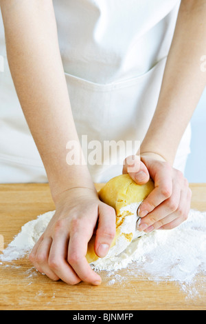 Hands kneading ball of dough with flour on cutting board - Stock Photo