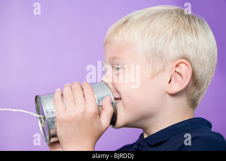 Boy talking on a tin can telephone - Stock Photo