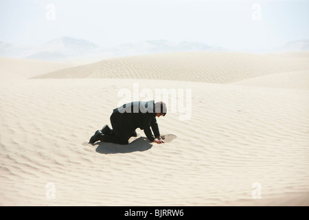USA, Utah, Little Sahara, mid adult businessman digging hole on desert - Stock Photo
