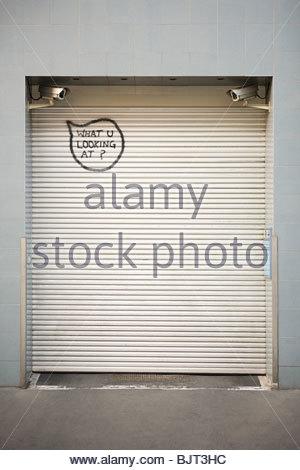 Graffiti written on a shutter - Stock Photo