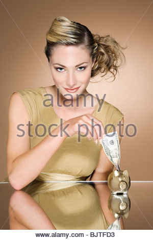 Woman putting cash in a piggy bank - Stock Photo