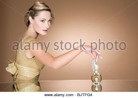 Woman putting cash in piggy bank - Stock Photo
