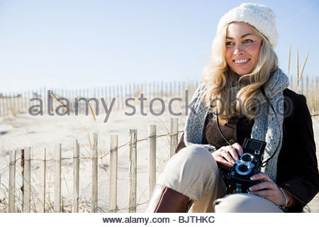 Woman at beach with camera - Stock Photo