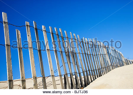 Wooden fence on a beach - Stock Photo