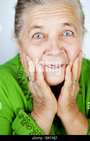 Excited senior woman with surprise expression on her face - Stock Photo