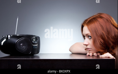 Young woman listening radio. Boring mood. - Stock Photo