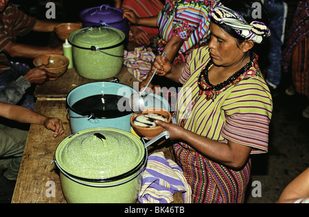 Women wearing traditional Maya clothing serving prepared food in Cantel, Guatemala - Stock Photo