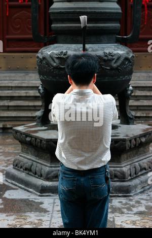 Prayer with incense in the Shanghai White Jade Buddha temple, Shanghai, China, Asia - Stock Photo