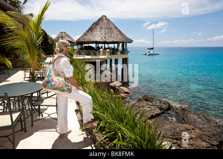Woman looking at the Sunset Beach Resort on a beach near Glacis, Mahe Island, Seychelles, Indian Ocean, Africa - Stock Photo