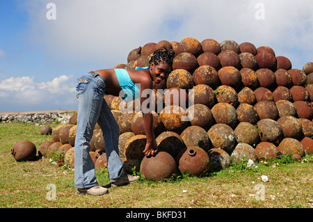 Local girl in front of Pile of Cannonballs, Citadel in Northern Haiti, Milot - Stock Photo