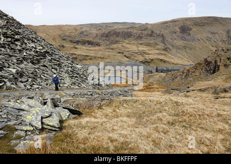 A hill walker climbing an incline on to Moelwyn Mawr from the ruins of the Rhosydd slate mine above Blaenau Ffestiniog - Stock Photo