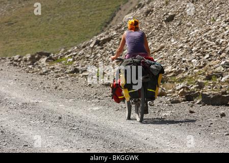 Female cyclist on a mountain road, Kyrgyzstan - Stock Photo