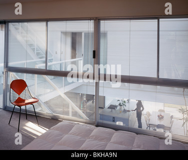 Charles Eames chair in front of glass wall with blinds in modern white bedroom overlooking open-plan living and - Stock Photo
