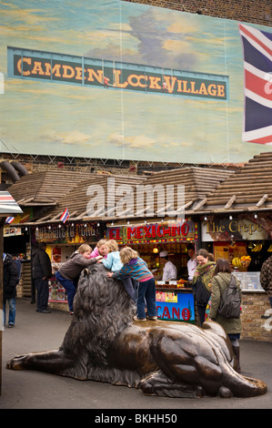 four children climbing over and playing on a bronze statue of a male lion in front of market stalls at Camden market - Stock Photo