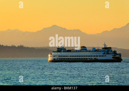 Washington state ferry in Elliott Bay with the Olympic mountains in the distance - Stock Photo