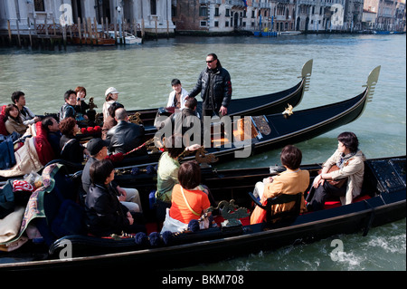 Gondolier singing opera arias to Japanese tourists in Gondolas on the Grand Vanal in Italy - Stock Photo